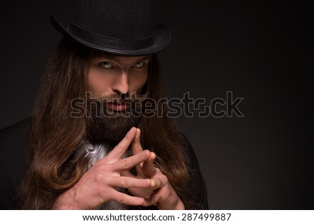 Serious long-haired magician thinking about hypnosis. Man with moustache having gimlet eyes. - stock photo