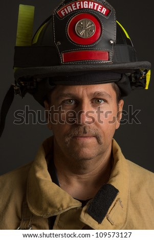 Serious looking confident firefighter Headshot Portrait on Dark Background - stock photo