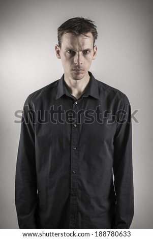 serious looking man on depressing grey background - stock photo