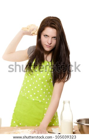 serious looking woman about to throwing dough in front of white background - stock photo