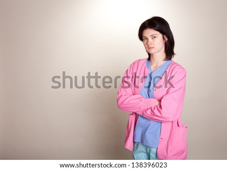 Serious looking young female doctor/nurse in scrubs with arms folded on light grey background - stock photo