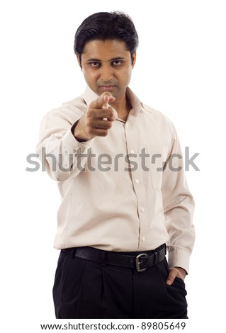 Serious looking young indian business man pointing finger at you isolated over white background - stock photo