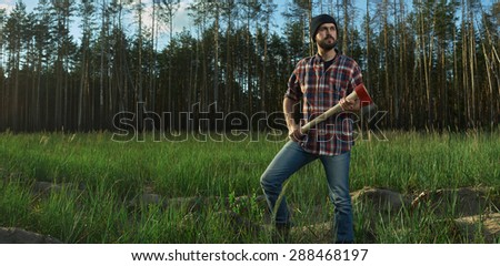 Serious Lumberjack with a big Ax in Hands in a Forest - stock photo