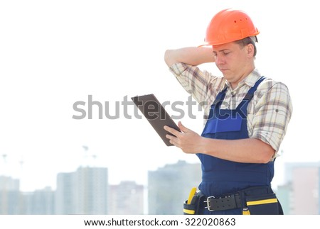 Serious male builder with electronic tablet in hands. Seating is on a new construction site. Male construction engineer with touch pad and checking building, site construction. Get important message - stock photo