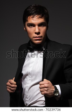 Serious male holding his jacket from a formal suite and looking at camera - stock photo