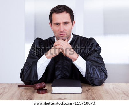 Serious Male Judge With The Gavel And Book In Courtroom - stock photo