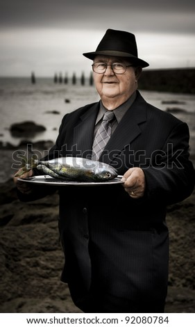 Serious Man At Dark Beachfront Holding A Plate Of Fish With A Questioning Expression In A Fisheries Over Consumption Of Natural Resources - stock photo