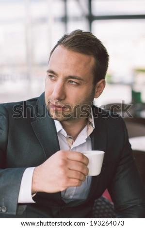 Serious man drinking espresso in cafe  - stock photo