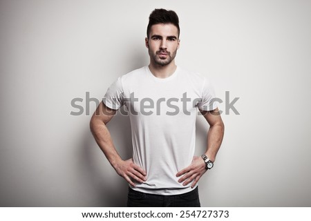 Serious man in blank t-shirt, white wall background - stock photo