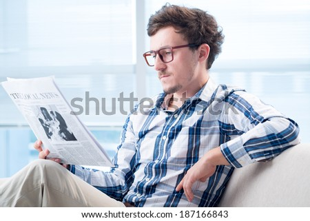 Serious man in glasses reading newspaper - stock photo