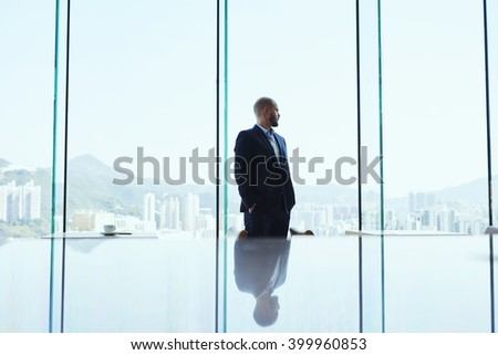 Serious man skilled financier is thinking about the crisis situations and methods of improving the situation, while is standing in modern office interior and watching in window on business district  - stock photo