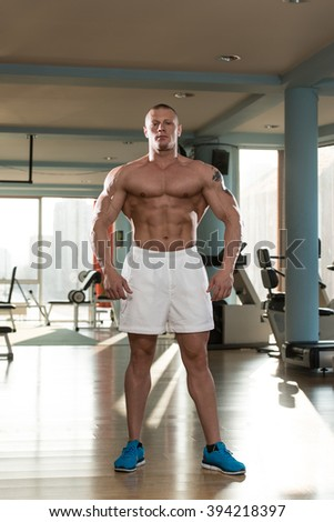 Serious Man Standing In The Gym And Flexing Muscles - stock photo