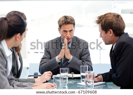 Serious manager talking to his team during a meeting in the office - stock photo