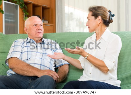 Serious mature couple talking in home interior. Focus on man - stock photo