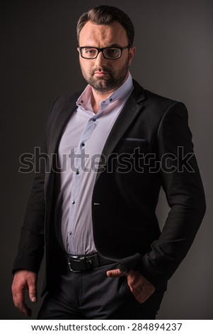 Serious mature man in suit posing on dark background. Studio shot. - stock photo