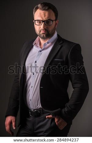 Serious mature man in suit posing on dark background. Studio shot. - stock photo
