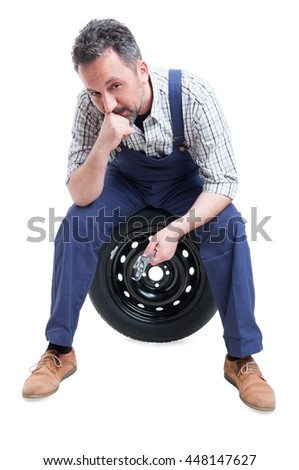 Serious mechanic man sitting on black tire looking at the camera isolated on white background - stock photo