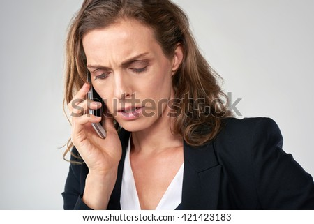 Serious middle age business woman talking on mobile cell phone smartphone, isolated in studio - stock photo
