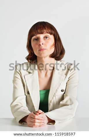 Serious middle age teacher sitting behind the desk - stock photo