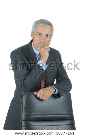 Serious Middle Aged Businessman leaning on chair back with hand on his chin isolated on white - stock photo
