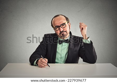 Serious middle aged businessman with glasses skeptically looking at you sitting at his desk isolated on office grey wall background. Human face expression, body language, attitude, perception  - stock photo