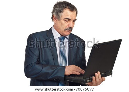 Serious middle aged executive man working on laptop isolated on white background - stock photo