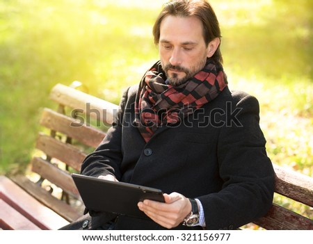 Serious middle-aged man looking at his tablet PC's screen. Man in black coat and with scarf on working on the bench outdoors. - stock photo
