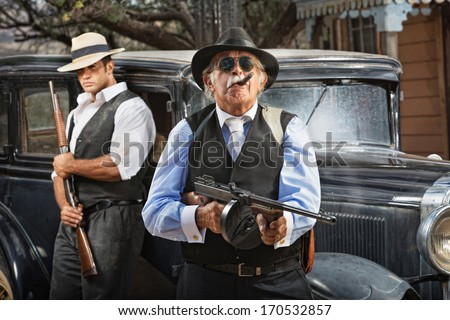 Serious mob boss with gun and guard near car - stock photo