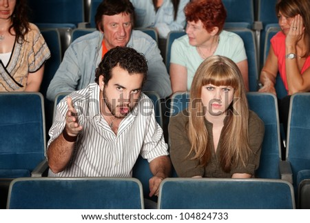 Serious movie fans angry in a theater - stock photo