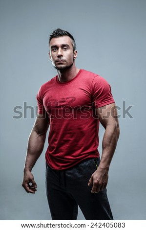 Serious muscular man in red t-shirt standing over gray background - stock photo