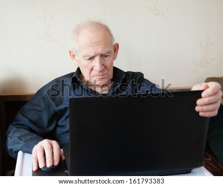 serious old man holding computer mouse - he is working on a laptop - stock photo