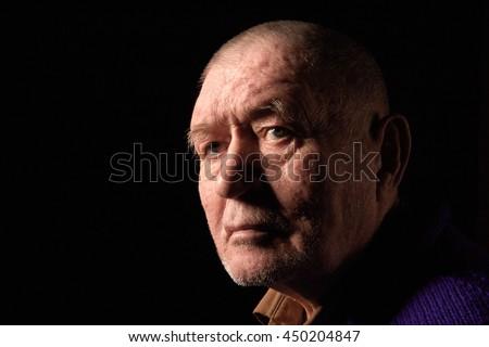 serious old man senior on black background - stock photo