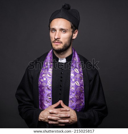 serious pastor. Studio portrait on black background    - stock photo