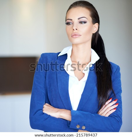 Serious pensive businesswoman in a stylish blue jacket standing with folded arms looking thoughtfully to the side - stock photo