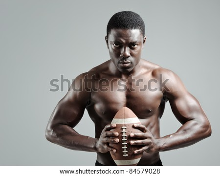 Serious portraits of a black american football sportsman in studio - stock photo
