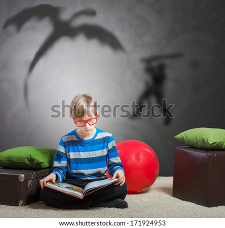 Serious preteen boy sitting on the floor and reading a story about a knight and a dragon - stock photo