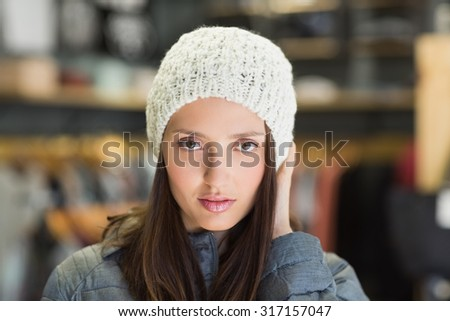 Serious pretty brunette looking at camera with winter clothes in clothes store - stock photo