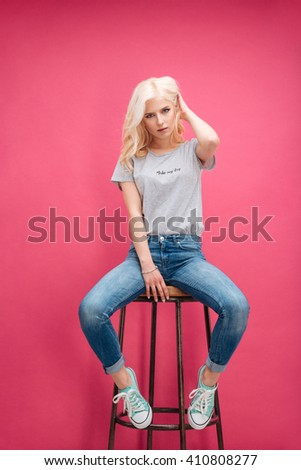 Serious pretty woman sitting on the chair over pink background - stock photo