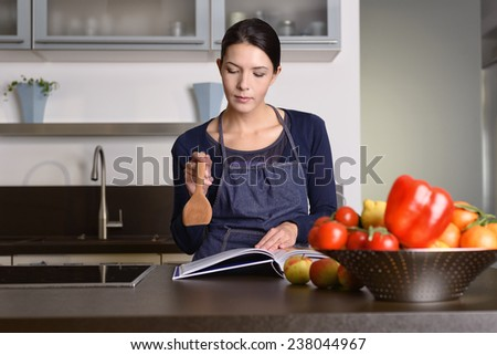 Serious Pretty Woman Wearing Apron Holding Wooden Ladle While Reading a Recipe Book at the Table with Fruits and Veggies in the Kitchen. - stock photo
