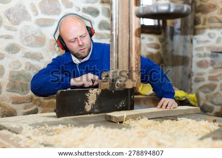 Serious professional worker working on a machine at wood workshop