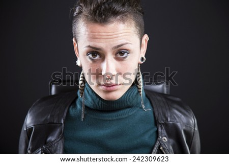 serious rocker girl on black background - stock photo