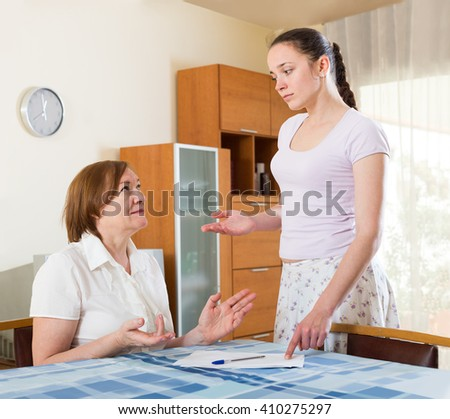 serious russian women with  documents at table in office interior - stock photo