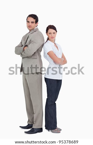 Serious sales team with arms folded standing back to back against a white background - stock photo