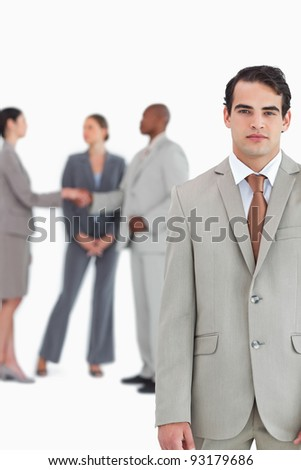 Serious salesman with businesspeople behind him against a white background - stock photo