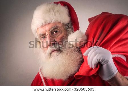 Serious Santa Claus holding a bag - stock photo