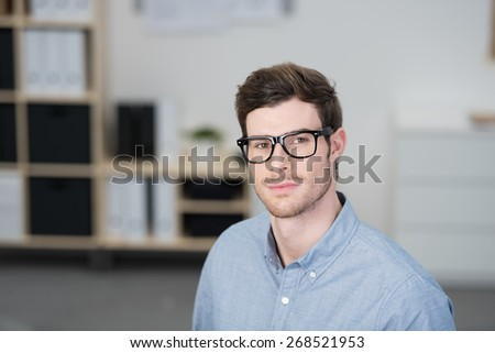 Serious scholarly young businessman wearing nerdy dark framed glasses looking directly at the camera, with copyspace - stock photo