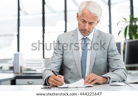 Serious senior businessman reading business documents in office. Senior manager reviewing quotation of company for contract. Portrait of executive senior planning new business project sitting at desk. - stock photo