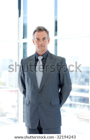 Serious senior businessman standing in office - stock photo