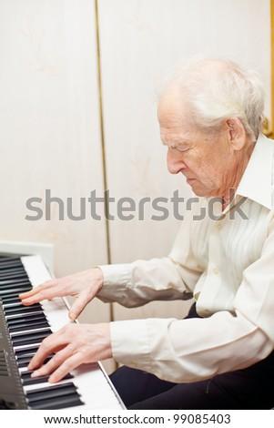 serious senior man playing piano - stock photo