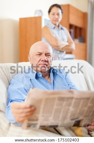 serious senior man reading newspaper against sad mature woman in home  - stock photo